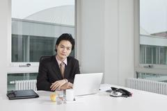 Portrait of a businessman sitting at his office desk Stock Photos