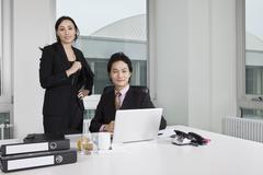A businessman and a businesswoman looking at a laptop Stock Photos
