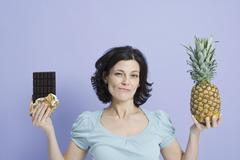 A woman deciding between a pineapple and a chocolate bar - stock photo