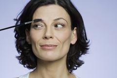Headshot of a woman applying makeup - stock photo