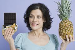 A woman deciding between a pineapple and a bar of chocolate - stock photo