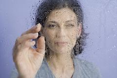 Stock Photo of A woman behind wet glass