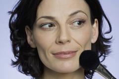 A woman applying face powder - stock photo