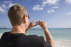 Stock Photo of Rear view of a man using a digital camera, Cable Beach, Nassau, Bahamas