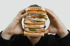 A man holding a large sandwich Stock Photos