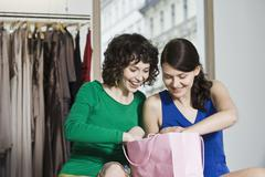 Two young woman in a clothing store Stock Photos