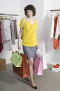 A young woman shopping in a clothing store Stock Photos