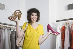 Stock Photo of A young woman holding two shoes in a store