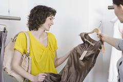 A sales assistant showing a young woman a dress Stock Photos
