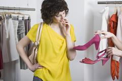A woman choosing between two shoes in a store Stock Photos