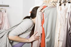 A woman searching through a clothes rail in a store Stock Photos