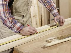 Detail of man marking piece of timber using pencil and tape measure Stock Photos