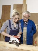 A man watching a woman sawing wood Stock Photos