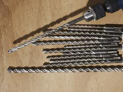 A drill and assorted drill bits on a bench Stock Photos