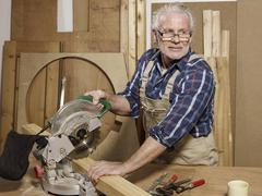 A man sawing wood in a workshop Stock Photos