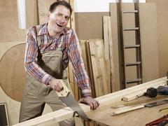 A man sawing wood Stock Photos