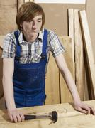 A young man leaning on a bench in a wood workshop Stock Photos
