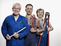 Three manual workers holding tools Stock Photos