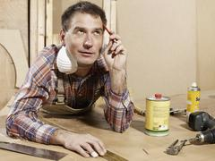A man leaning on a workbench and thinking Stock Photos