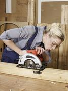 A woman sawing wood Stock Photos