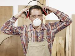 A man putting on protective workwear - stock photo