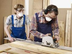 Two men cutting wood in a workshop - stock photo