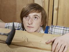 A young man behind a bent nail in wood Stock Photos