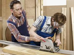 A man assisting a young man sawing wood Stock Photos
