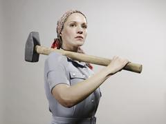 A woman holding a sledgehammer over her shoulder Stock Photos