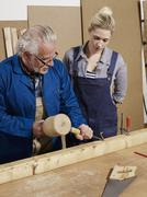 A man demonstrating wood chiseling to a woman in a workshop Stock Photos