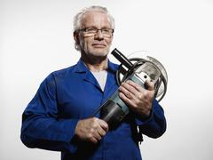 A man clutching a circular saw Stock Photos