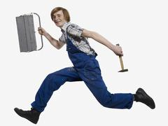 A young man running with a tootlbox and hammer - stock photo