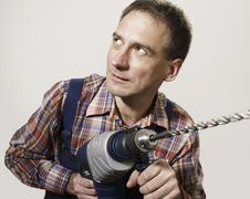 A man holding a large drill - stock photo