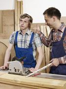 Two men standing at a workbench - stock photo