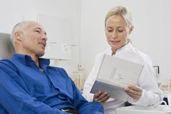 A dentist talking to a patient sitting in a dentist's chair Stock Photos