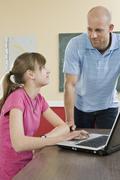 A schoolgirl using a laptop with a teacher standing beside Stock Photos