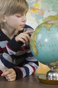 A schoolboy looking at a globe Stock Photos