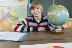 Portrait of a schoolboy sitting near a globe Stock Photos