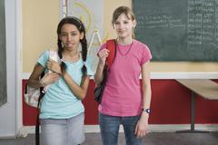Kaksi koulutytöt seisoo vierekkäin - stock photo