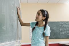 A girl writing on a blackboard in a classroom Stock Photos