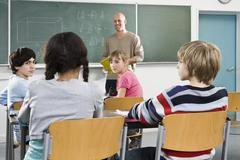 Students and a teacher in a classroom Stock Photos