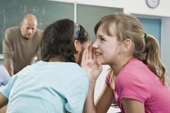A schoolgirl telling a secret to a friend - stock photo