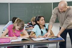 A teacher working with students in a classroom Stock Photos