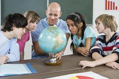 A teacher and students looking at a globe Stock Photos