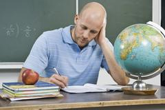 A teacher working at a desk Stock Photos