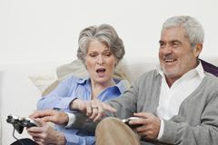 A senior man and senior woman playing a video game - stock photo