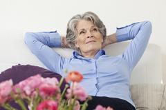 A senior woman relaxing in a living room Stock Photos