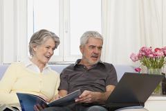 A senior woman and senior man using a laptop Stock Photos