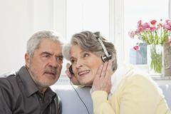 A senior woman sharing her headphones for a senior man to listen Stock Photos