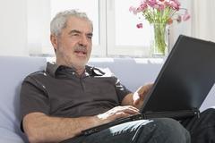 A senior man using a laptop Stock Photos